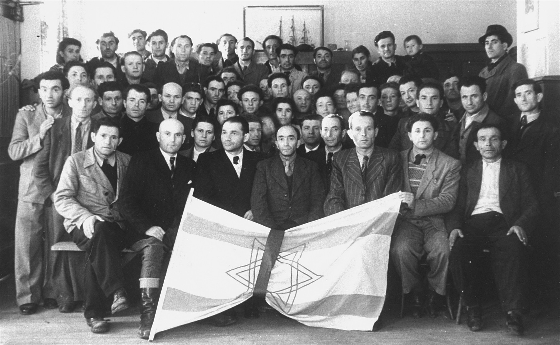 Group portrait of Jewish displaced persons holding a Zionist flag.  (Possibly a reunion of survivors from Lukow, Poland)