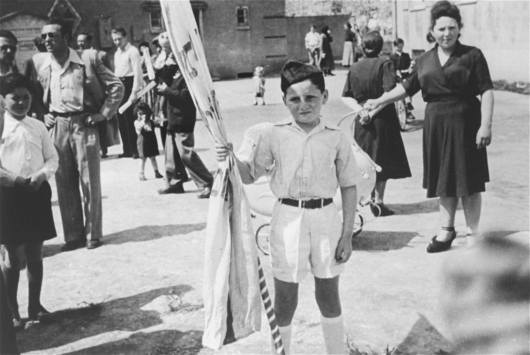A young Jewish DP child, dressed in the uniform of the Betar Zionist movement, poses with a flag during a ceremony celebrating the establishment of the State of Israel at the Heidenheim displaced persons camp.  Pictured is Itzhak Gersten.  His aunt, Basia, stands on the right.
