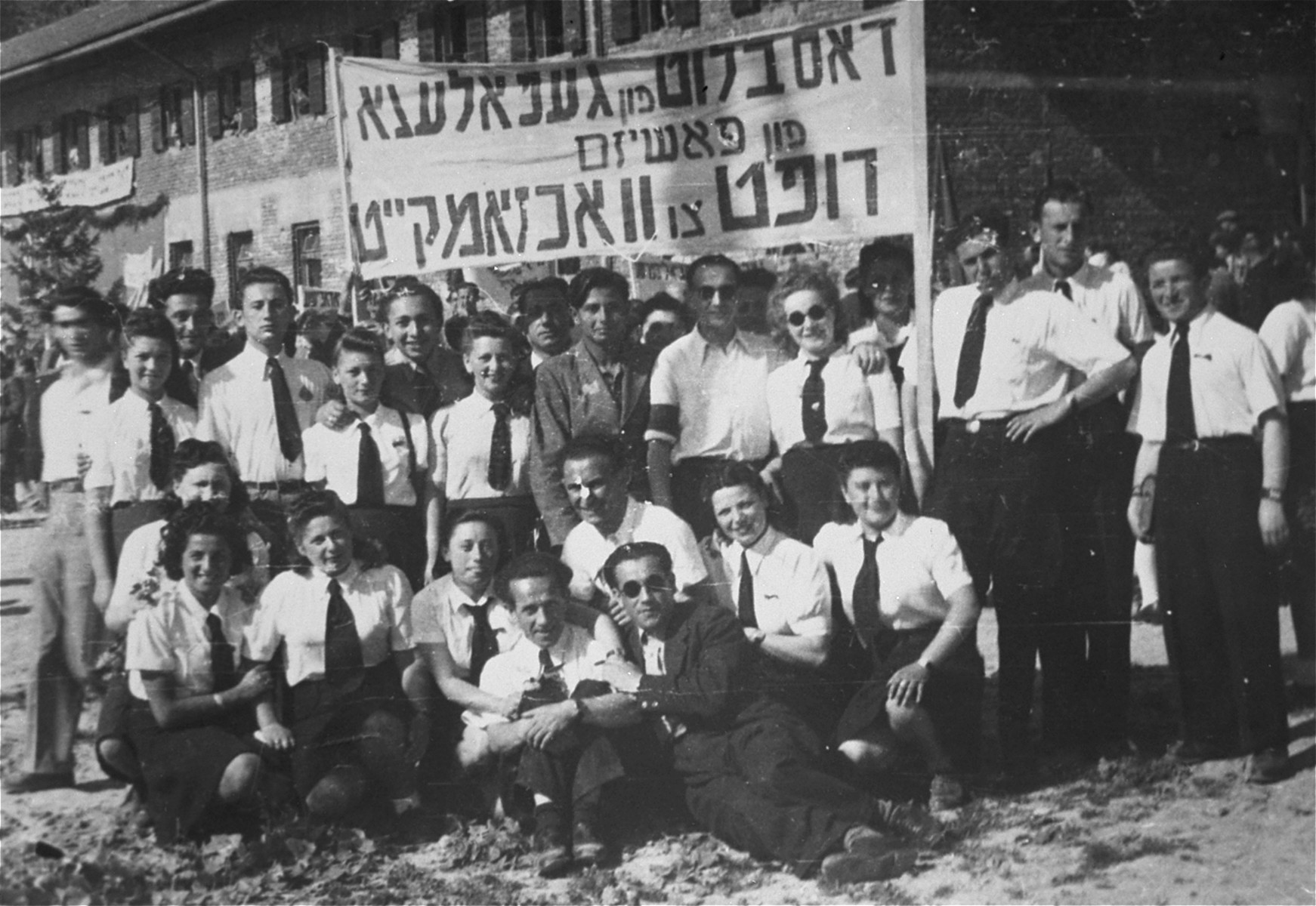 "Jewish musicians and actors in the Feldafing displaced persons camp pose beneath a Yiddish banner that reads: ""The blood of the victims of fascism calls for vigilance.""  Among those pictured is Leybl Fingerhut (front row in sunglasses)."