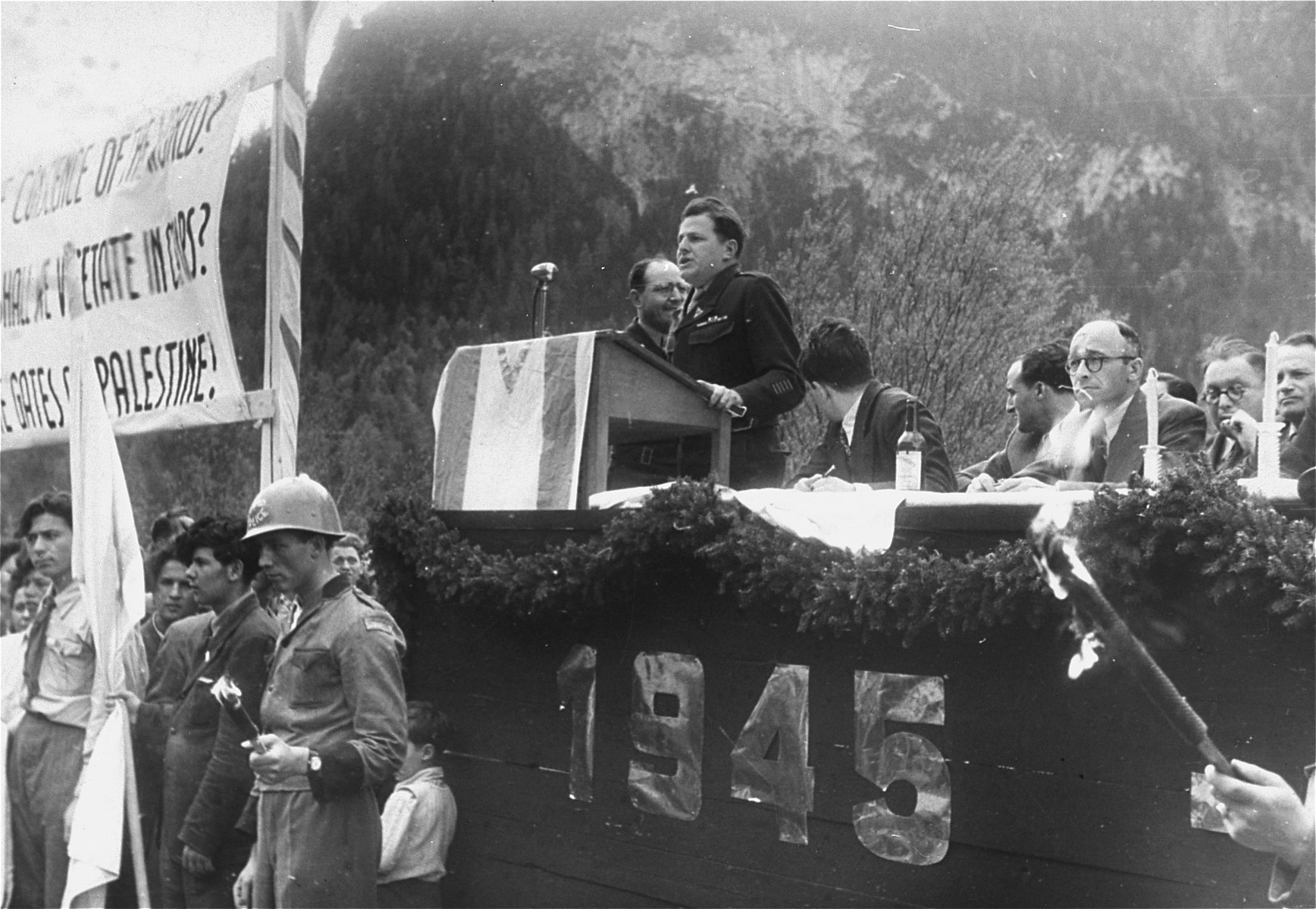 A speaker addresses an outdoor assembly of Jewish DPs held in the Mittenwald displaced persons camp to protest British immigration policy in Palestine and to commemorate the death march from Dachau to Tyrol.