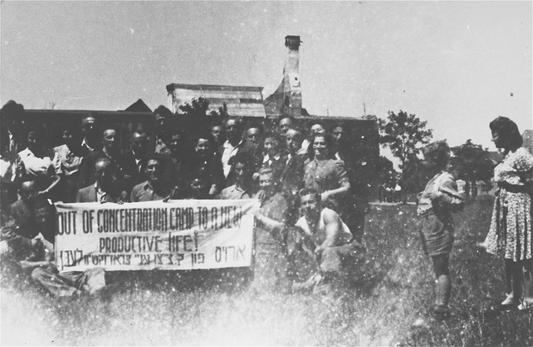 Jewish DPs in the Feldafing displaced persons camp hold a banner written in English and Yiddish, demanding that they be allowed to immigrate to Palestine.