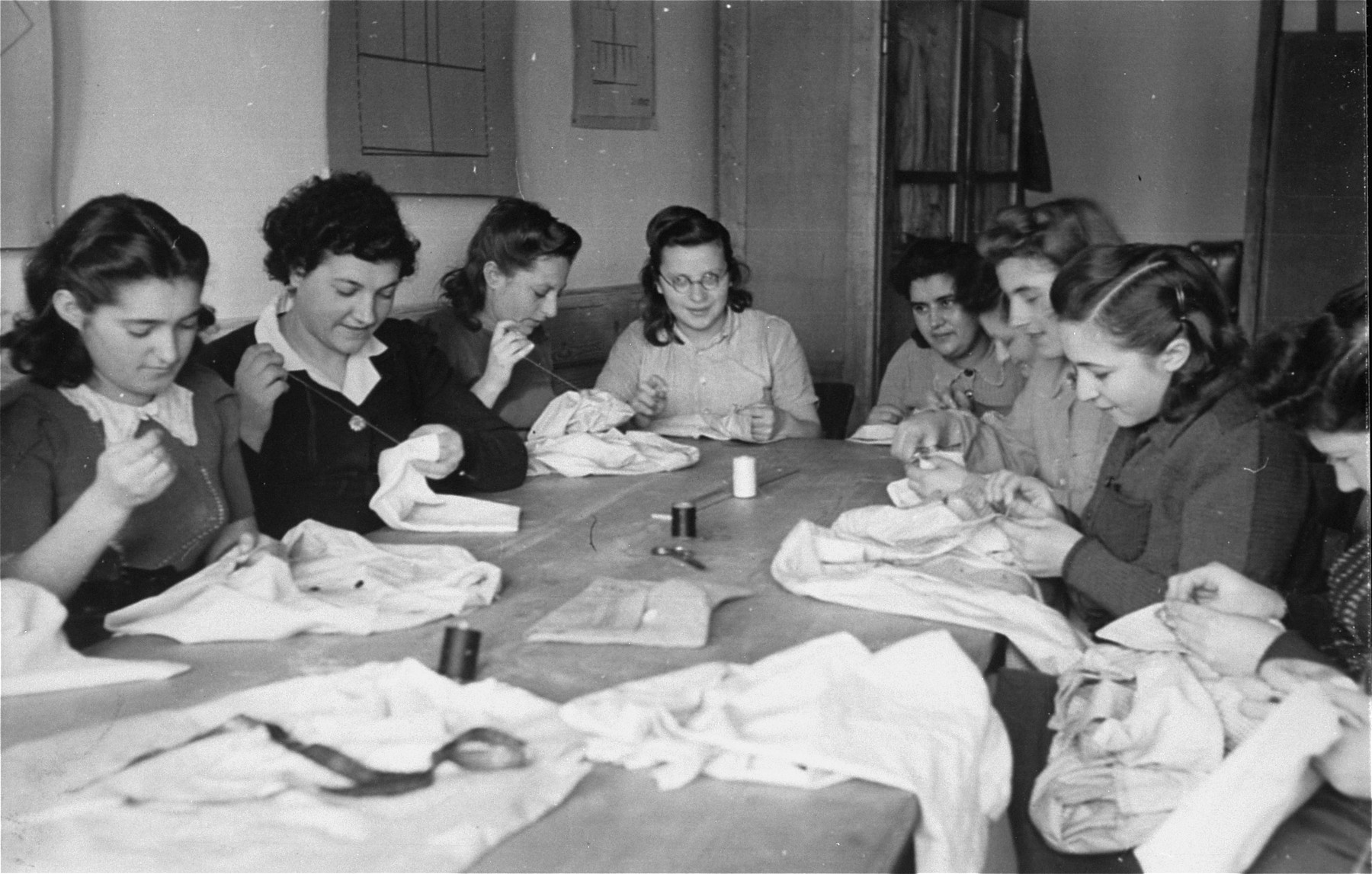 "A group of women sit around a table and hand-sew garments in an ORT (Organization for Rehabilitation through Training) workshop in the Landsberg displaced persons' camp.   Yiddish caption on the back: ""Pioneer women of different kibbutzim (locations in Europe), learning to sew in ORT school"". [Oversized print]"