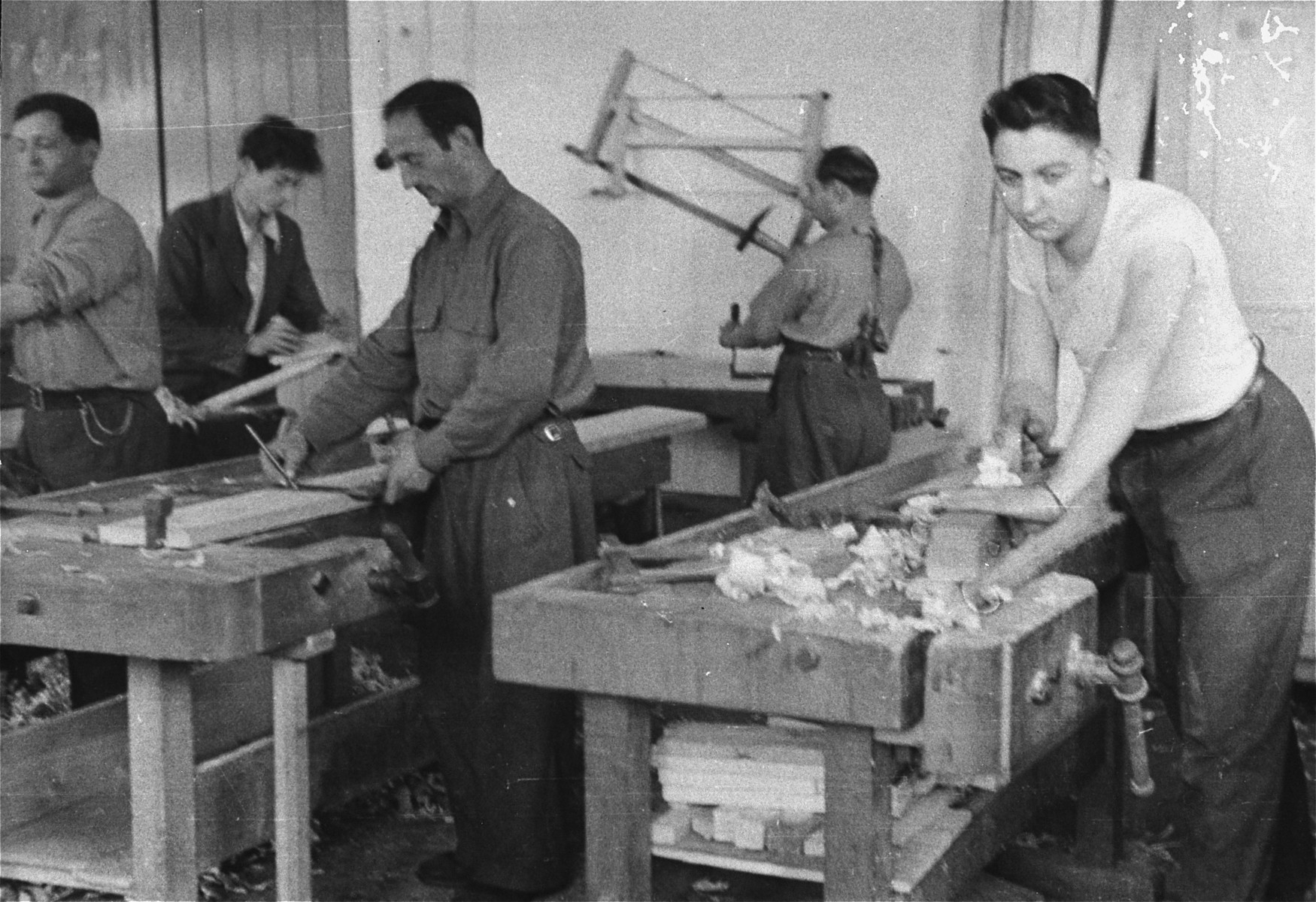 Jewish men measure and plane wood in the carpentry workshop of an ORT (Organization for Rehabilitation through Training) training program in the Landsberg displaced persons' camp: [Oversized print]