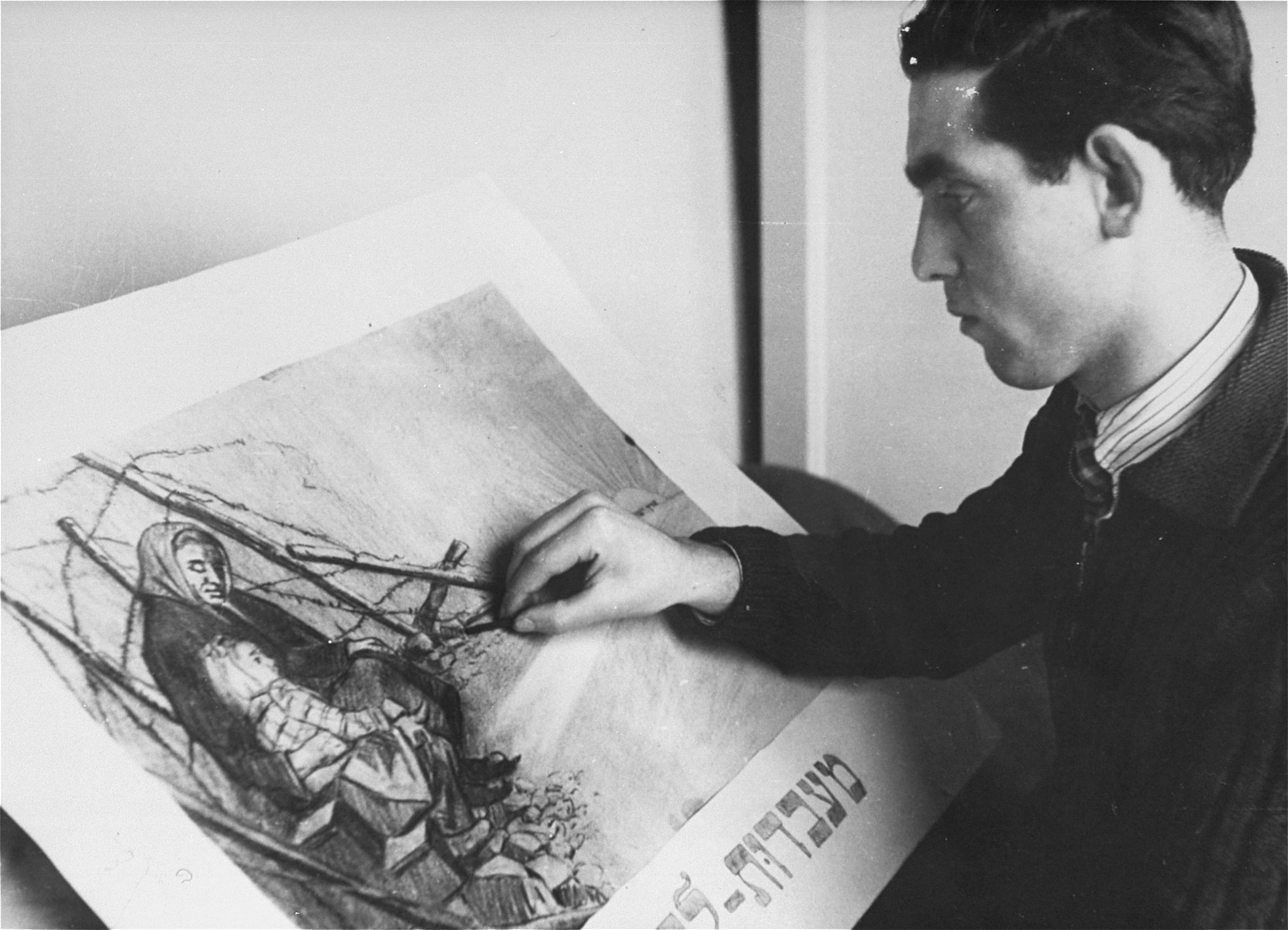 """Metzger, a young artist in the Landsberg displaced persons' camp, works on a charcoal drawing entitled """"From Slavery to Freedom""""."""
