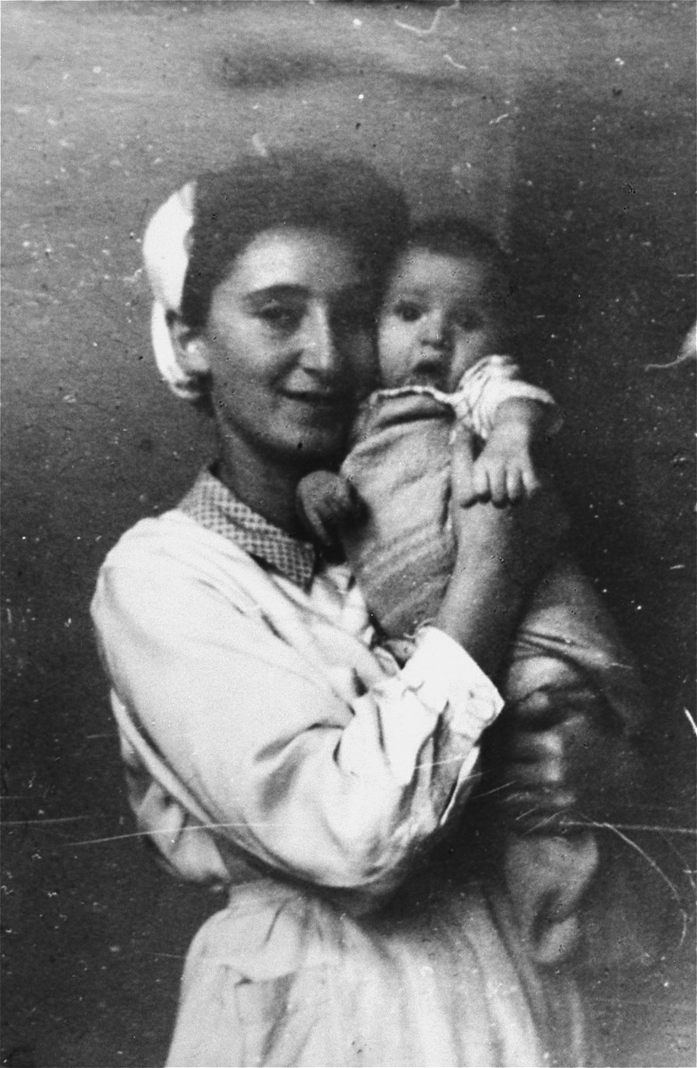 Tonia Rotkoff, a nurse at the UNRRA house in the Landsberg DP camp, holds a young baby.