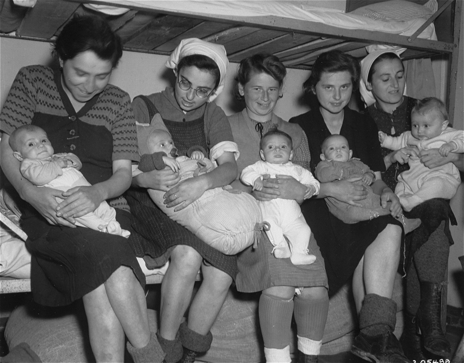 Group portrait of five Hungarian Jewish mothers and their infants in a Dachau sub-camp in Germany.  Pictured from left to right are:  Ibolya Kovacs with her daughter Agnes; Suri Hirsch with her son Yossi; Eva Schwartz with her daughter Maria; Magda Fenyvesi with her daughter Judit; and Boeszi Legmann with her son Gyuri.  Not pictured are: Dora Loewy and her daughter Szuszi; and Miriam Schwarcz Rosenthal and her son Laci (Leslie).