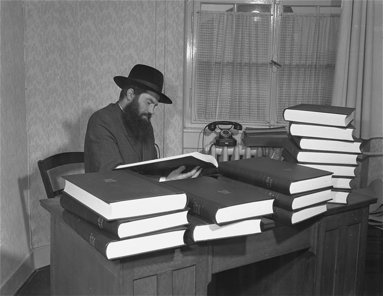 Rabbi Samuel Jakob Rose, Rabbi of the American zone of occupation in Germany, and a survivor of Dachau, examines one of the newly printed volumes of the Talmud.    This is the first edition of the Talmud to be printed in Germany since Kristallnacht.