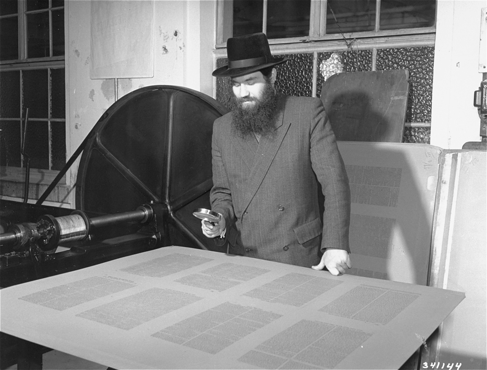 Rabbi Samuel Jakob Rose, rabbi of the American zone of occupation in Germany, and a survivor of Dachau, examines the galleys of the first postwar edition of the Talmud to be printed in Germany.