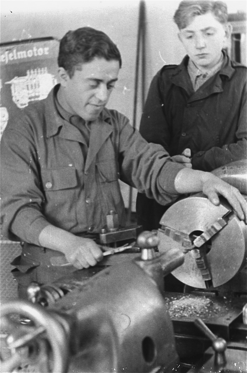 Two men work with a piece of machinery in an ORT (Organization for Rehabilitation through Training) metal workshop training program in the Landsberg displaced persons' camp. [Oversized print]