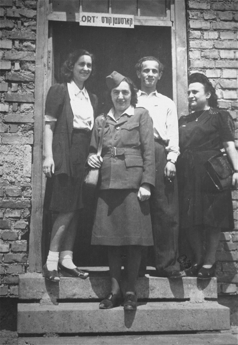Jewish DPs pose with an ORT representative at the entrance to a workshop in the Feldafing displaced persons camp.   Among those pictured is Chana Dina Leah Warszawska (first from the left).