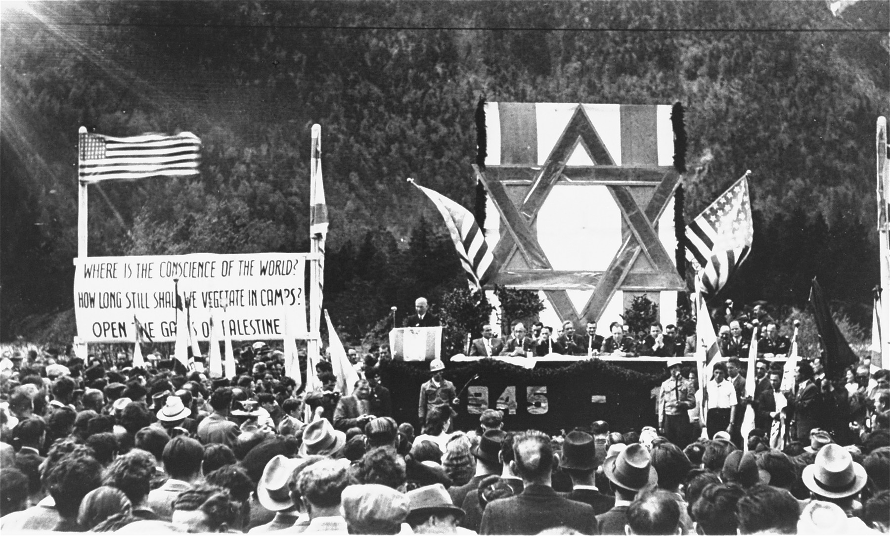 David Treger, President of the Central Committee of the Liberated Jews in Bavaria, delivers an address at a public meeting held in the Mittenwald displaced persons camp to protest British immigration policy in Palestine.    The banners call for free immigration to Palestine.