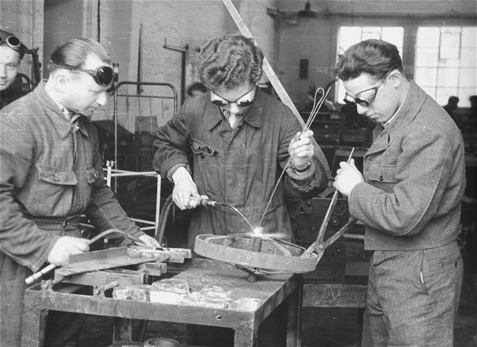 Three men practice welding in an ORT (Organization for Rehabilitation through Training) vocational training program in the Landsberg displaced persons' camp. [Oversized print]