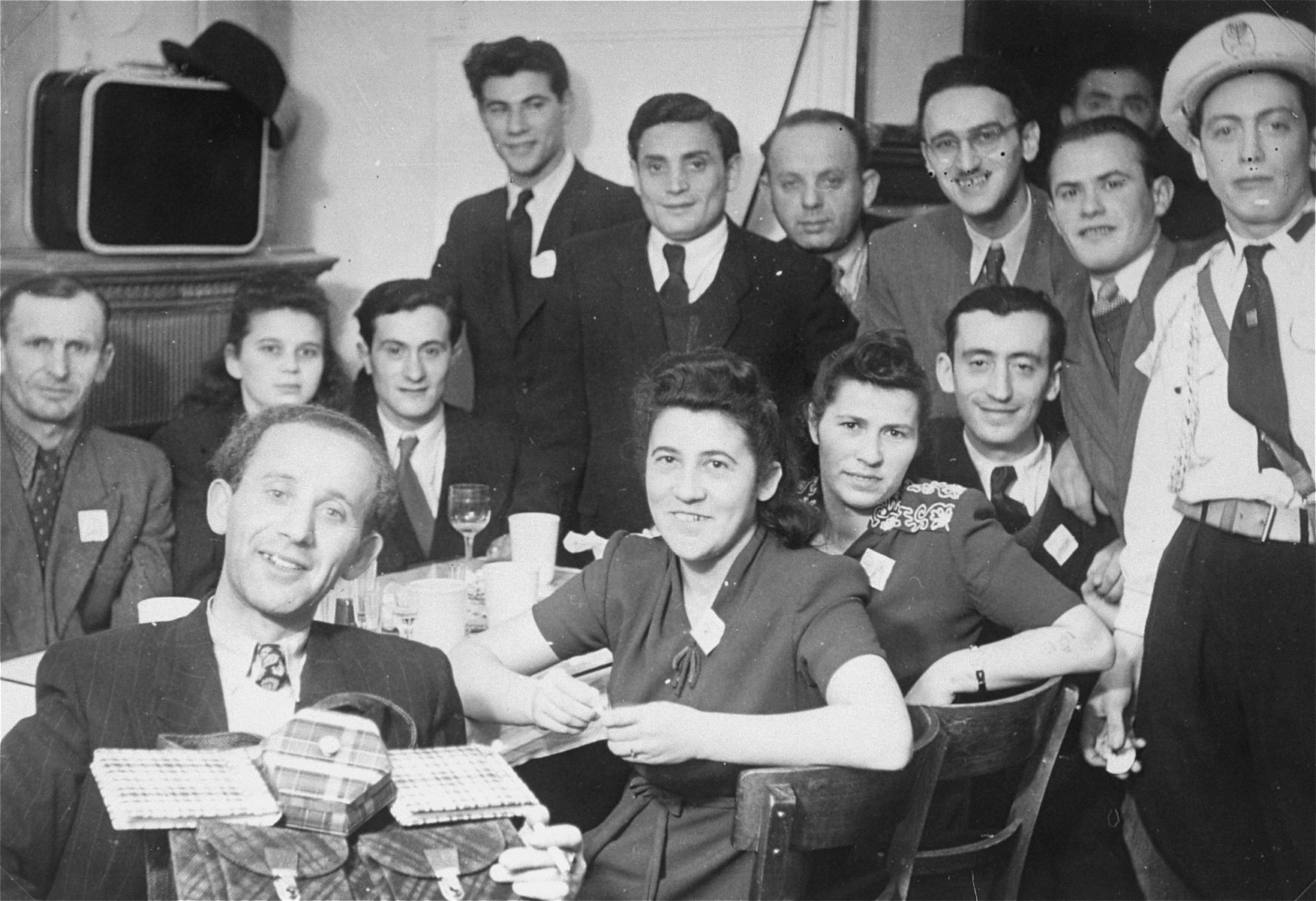 Group portrait of Jewish DPs gathered around a table in the Mittenwald displaced persons camp.