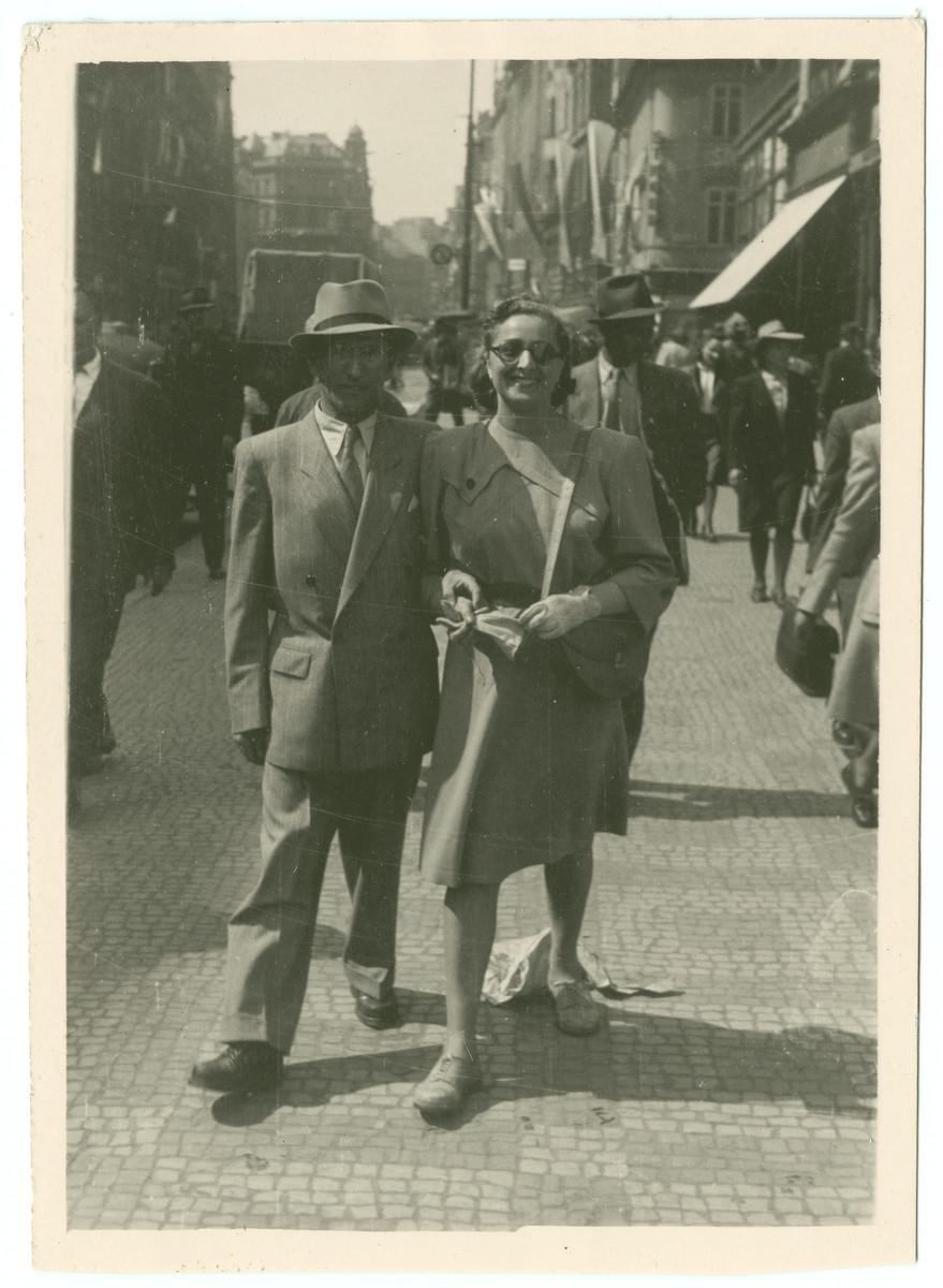 Rabbi and Mrs. Samuel Freilich walk down a street in Prague.