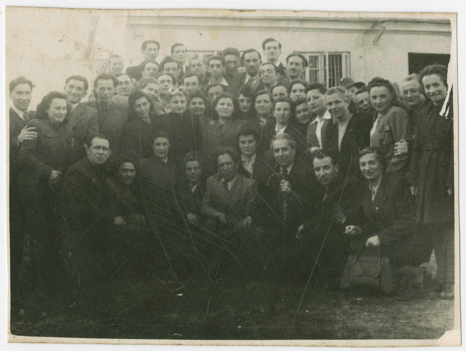 Postwar photograph of survivors from the Kovno and Vilna ghettoes together with the Soviet Jewish author, Ilya Ehrenberg.  Most of those pictured were partisans.  The donor Moshe Magidowitz is in the top, center.  Standing second from the left Shulamita Gelperninie, seated Meir Grinberg and Masha Endlin (third from left).  Also pictured are Naum Endlin (standing 4th from left), Chane Grinbrg (standing 6th from left), Sara Gordon, Sima Bloch, Alte Tepper, Chane Smuileva (under Sima Bloch), Pesach Shattner, Levin, Faitelson (second from right), Rochele Lifshitz, Opnitzki, Sara Ginaite (5th from left partially obscured), Lova Sher (middle),  Meir Yellin (top row, third from right), Pesach Wolbe, Mira Wainer, Moishe Rubinson, and Dovid Markovsky.