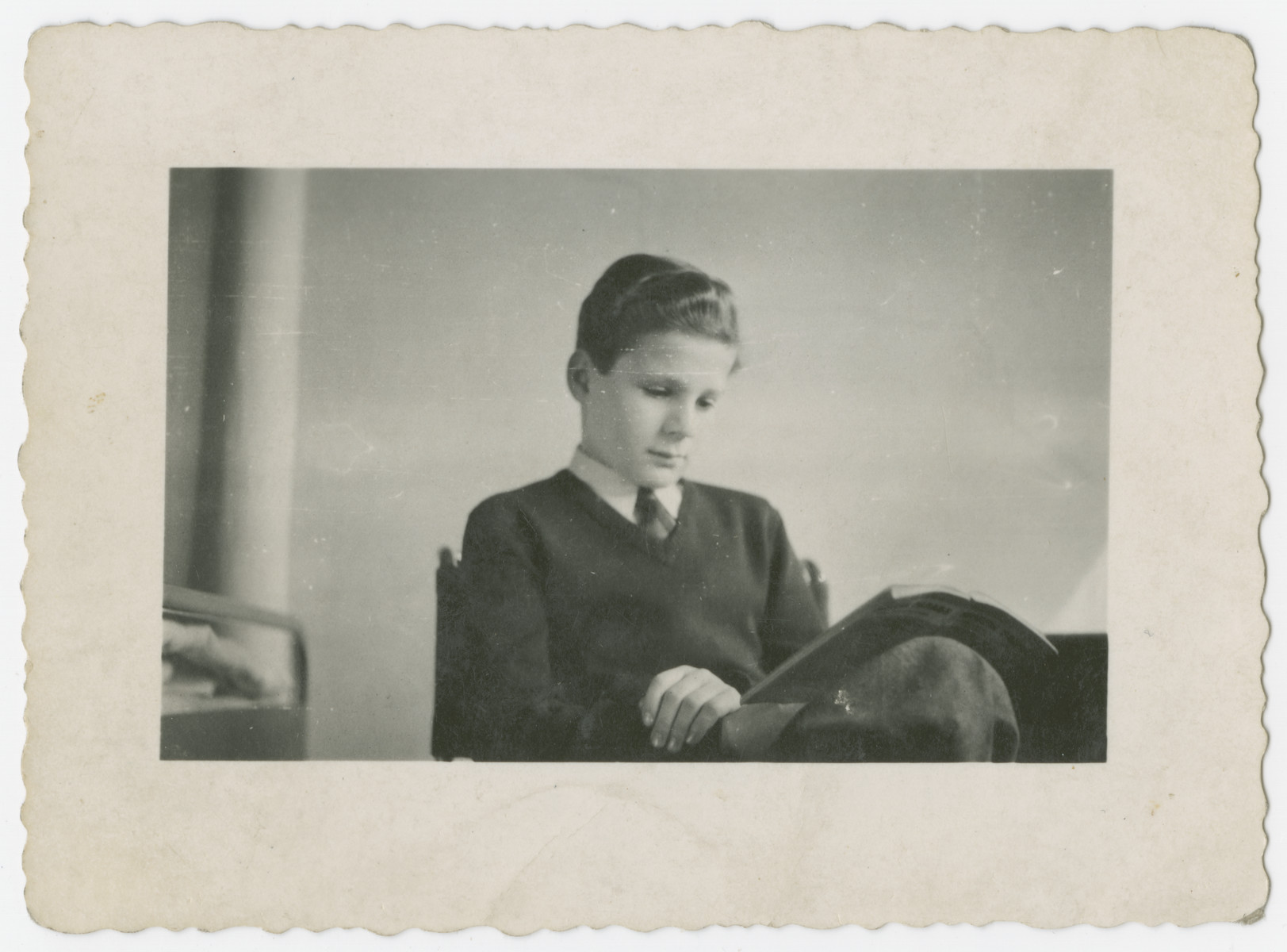 Child survivor, Misa Grunwald, reads a magazine after his return to Prague.