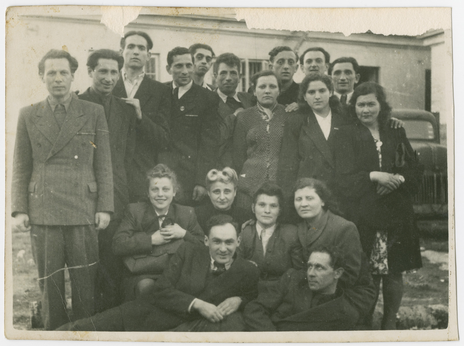 Postwar photograph of partisans from the Kovno ghetto.  The photo was probably taken in Trakai.  Bottom row:  Upniczki, Meyer Grinberg Second row seating: Mira Vainer Joels, ?, Chaya Smuilova, [Sara Gordon possibly]. Standing: Naum Endlin, LolikJoels, the tall man was a non-Jewish Communist who assisted the partisans and became the second husband of Chaya Smuilova and the mayor of Trakai, Simon Bloch, Moshe Magidowitz , Chone Kagan, Alte Borochovitch Tepper, Riva Bloch, Henela ?, Eliezer Zilber, Faitelson, and ?