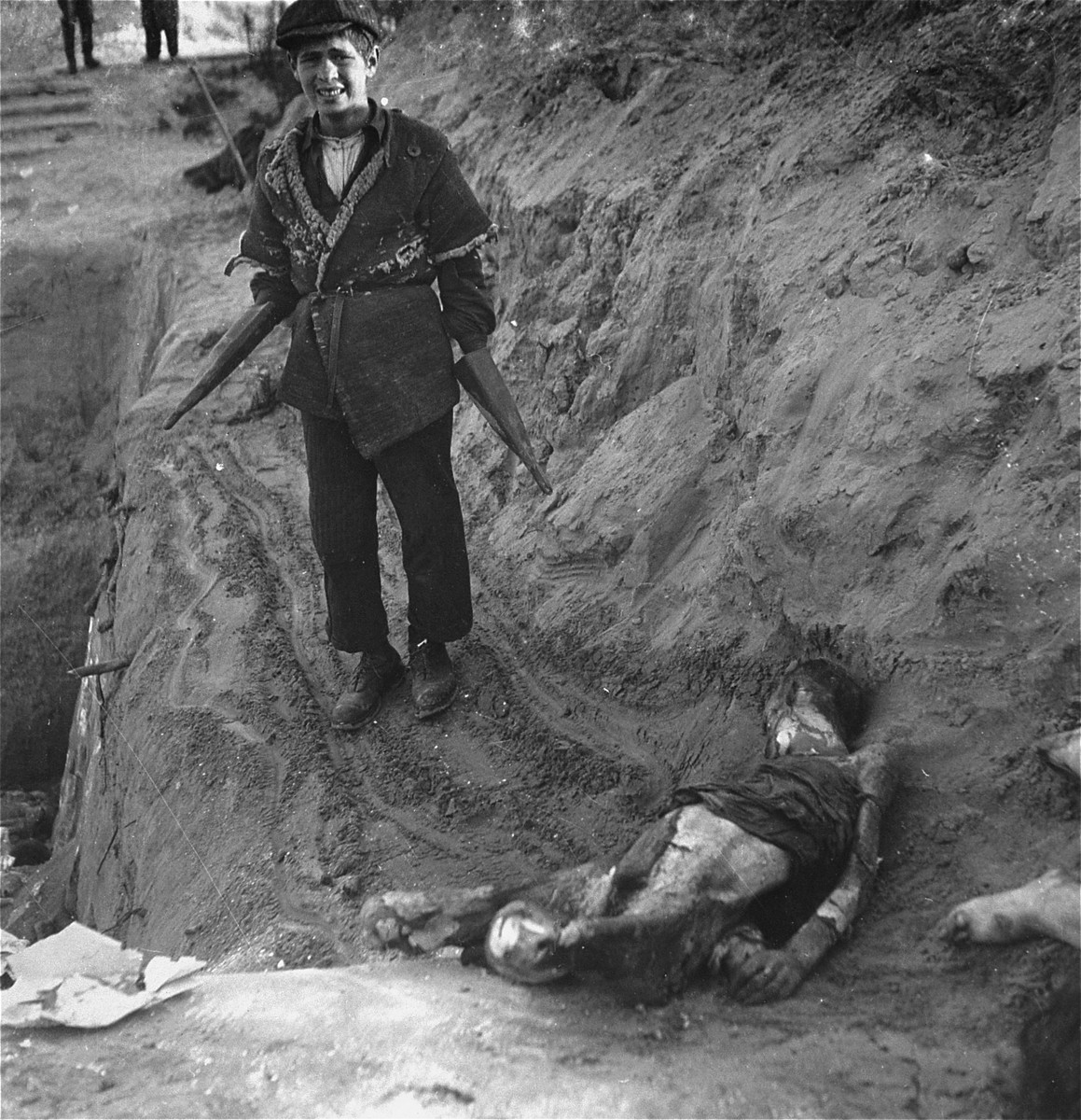 "A boy at work burying bodies in the Warsaw ghetto cemetery pauses for Heinrich Joest to photograph him.    Joest's caption reads: ""Himself still half a child, this youth belonged to the Jewish corpse-bearers: he showed me how he took hold of the corpses with his remarkable gloves, pulled them to the edge of the grave and let them slide down."""