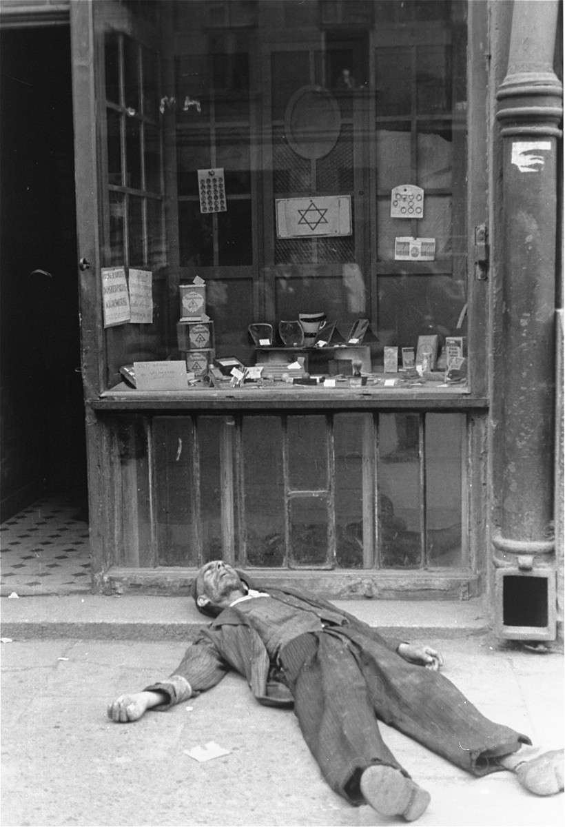 A man lies dead on the pavement in front of a shop in the Warsaw ghetto.