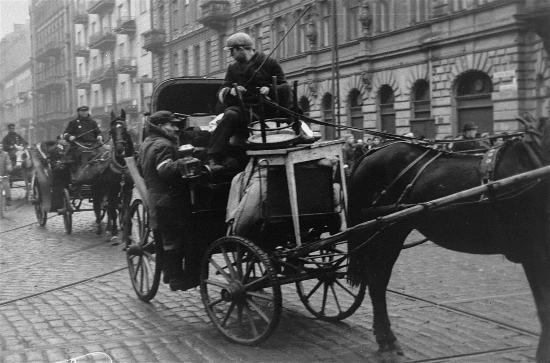 A driver leads a horse-drawn carriage along a street in the Warsaw ghetto.