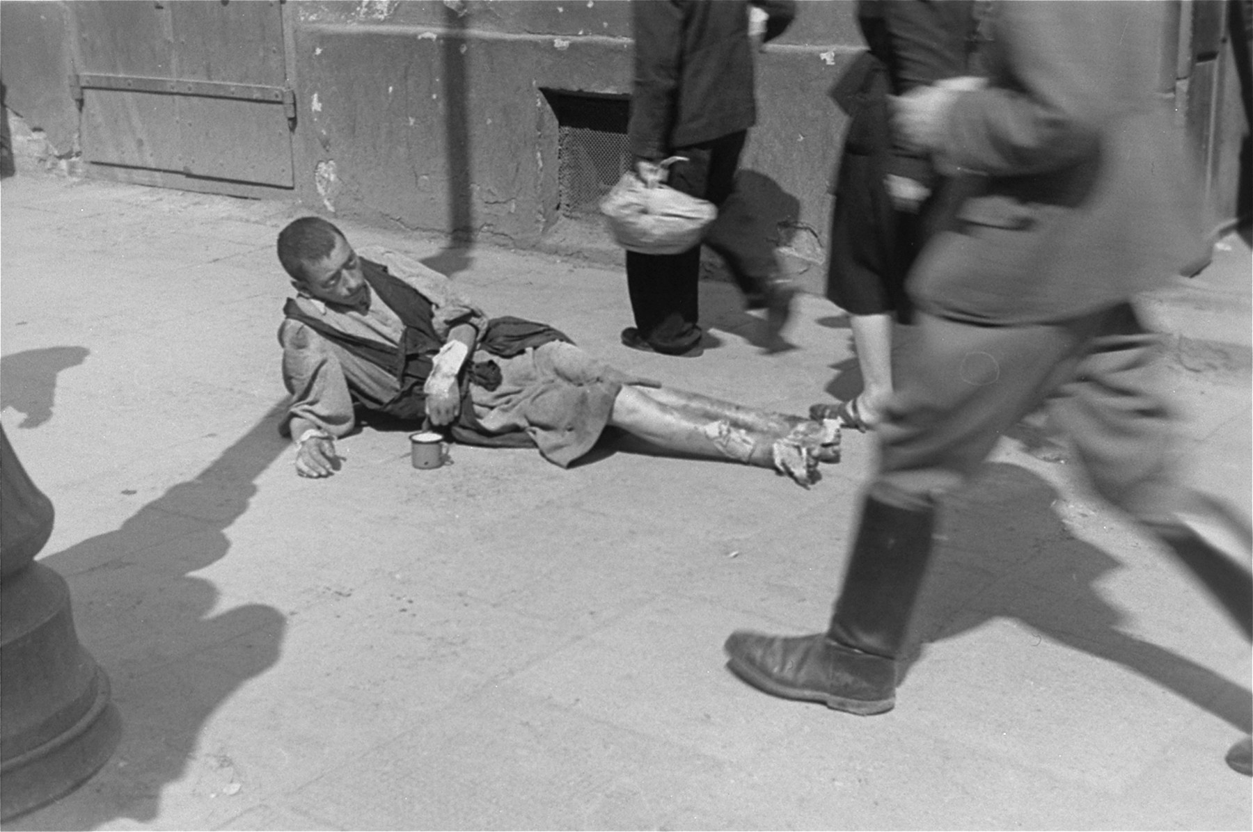 A destitute young man lies on the street in the Warsaw ghetto with a collection cup.