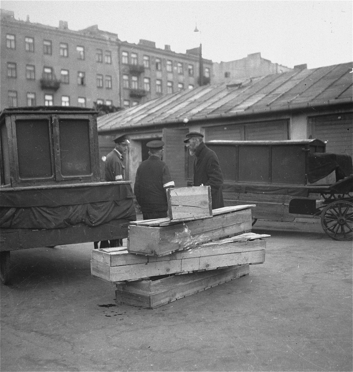 "Jewish undertakers converse next to a pile of wooden coffins in the Warsaw ghetto.    Joest's caption reads: ""The wooden crates being used as coffins were nailed shut more than once.  One could see bodies through the cracks."""