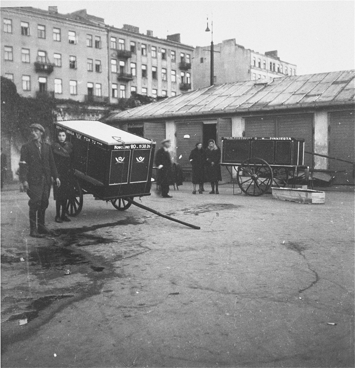 "Funeral wagons, cemetery staff, and other people on the grounds of the Jewish cemetery on Okopowa Street in the Warsaw ghetto.    Joest's caption reads: ""The funeral wagons lingered in the Jewish cemetery.  I did not know at the time of course that many of these had double walls and floors."""