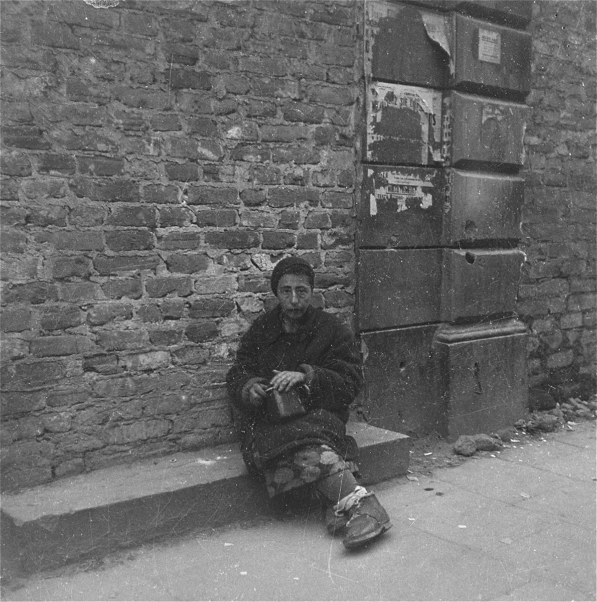 "A destitute woman on the street in the Warsaw ghetto.  Joest's caption reads: ""I believe that this woman was a black-marketeer offering something or other for sale.  She fearfully hid the pot in front of me and was thoroughly afraid around the police."""