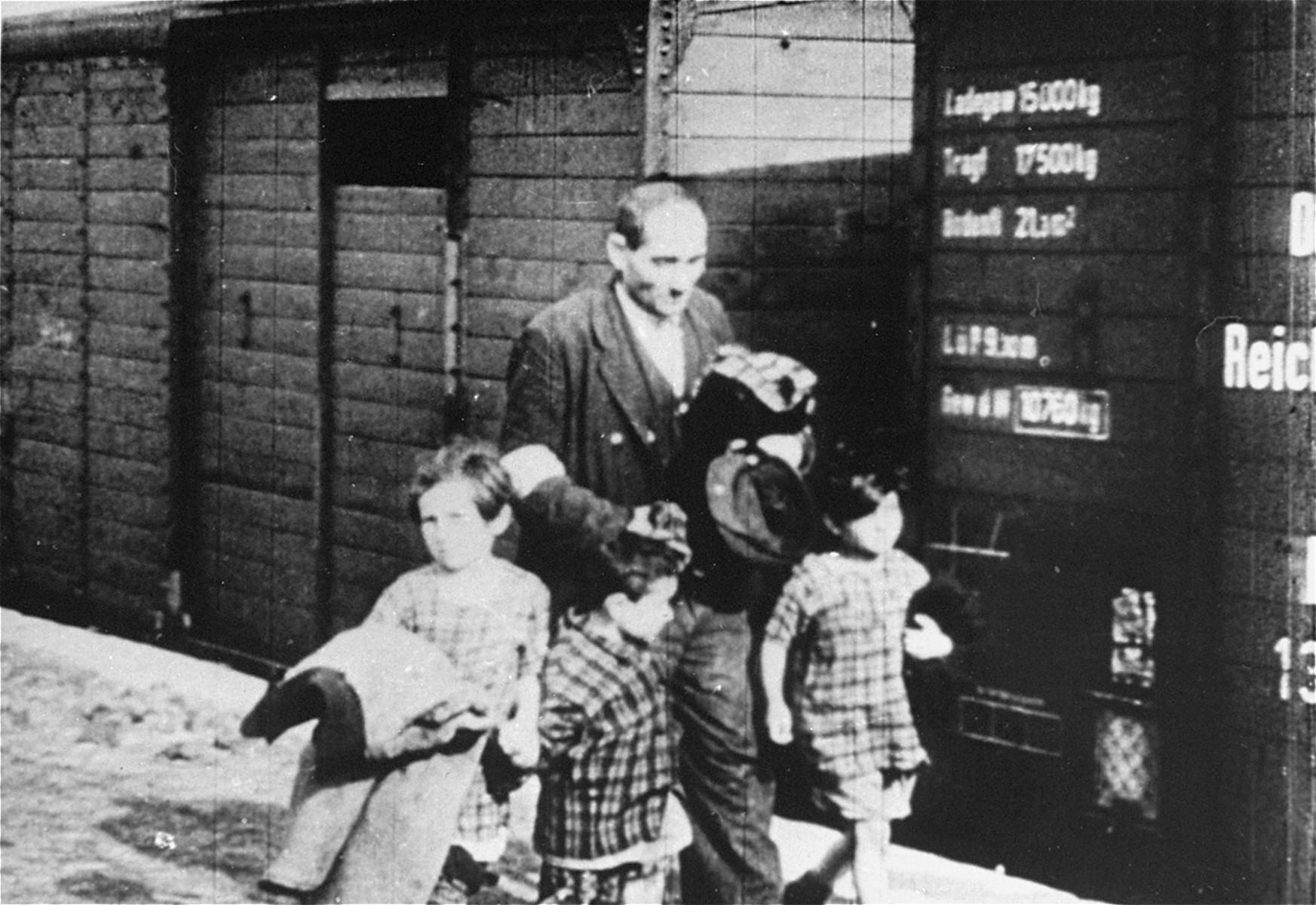 A Jewish man walks with three young children alongside a deportation train.
