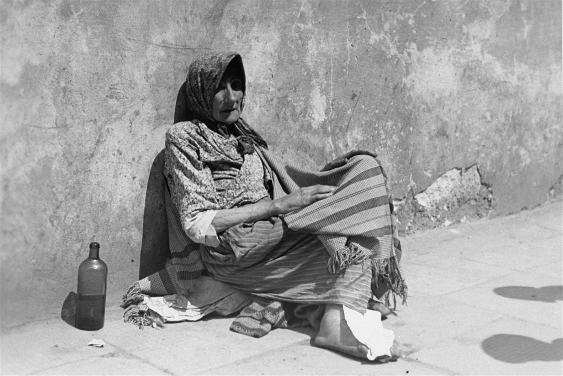 A destitute Jewish woman sits against a wall on the street in the Warsaw ghetto.