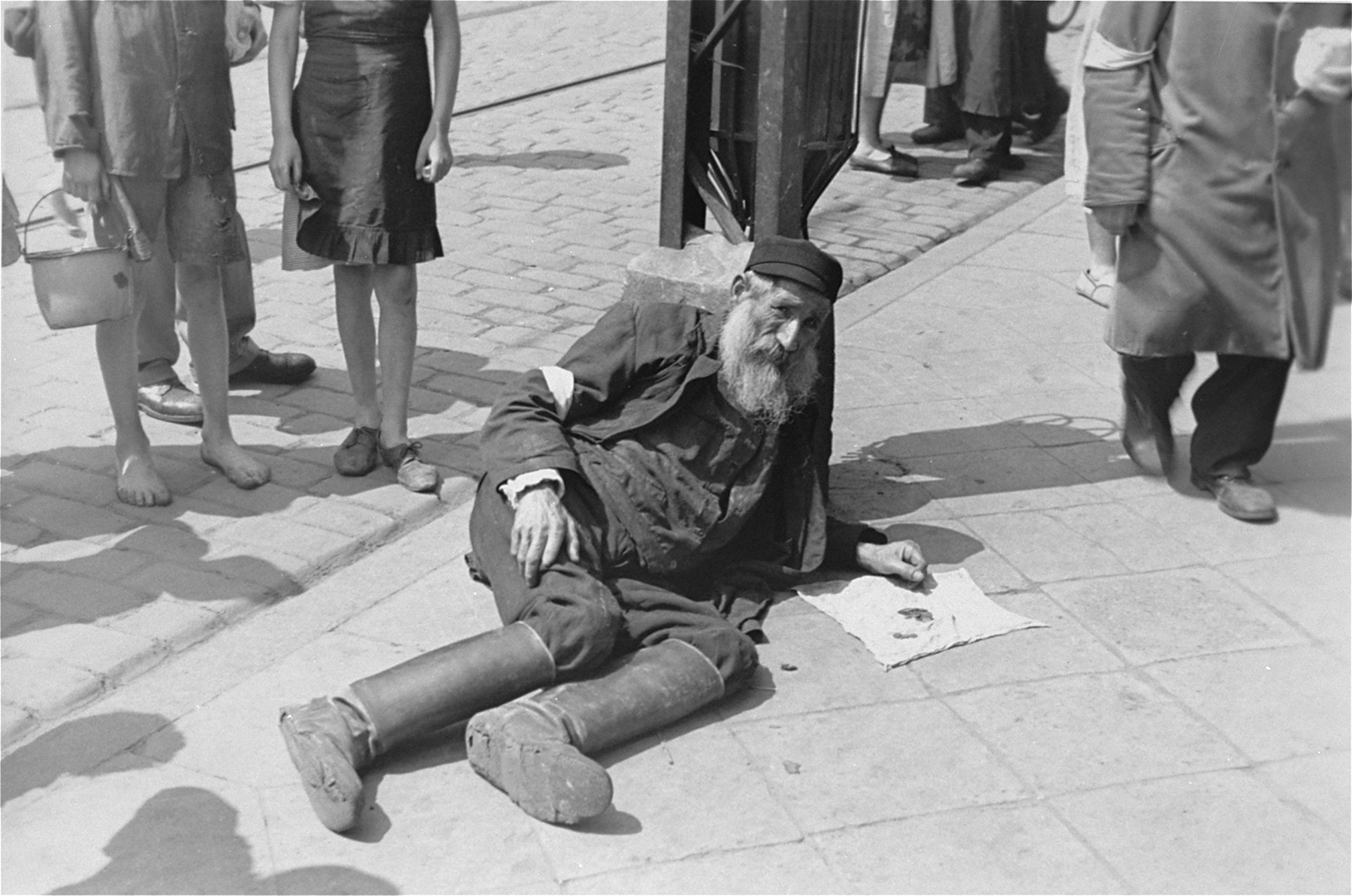 A destitute, elderly man lies on the pavement in the Warsaw ghetto begging for assistance.