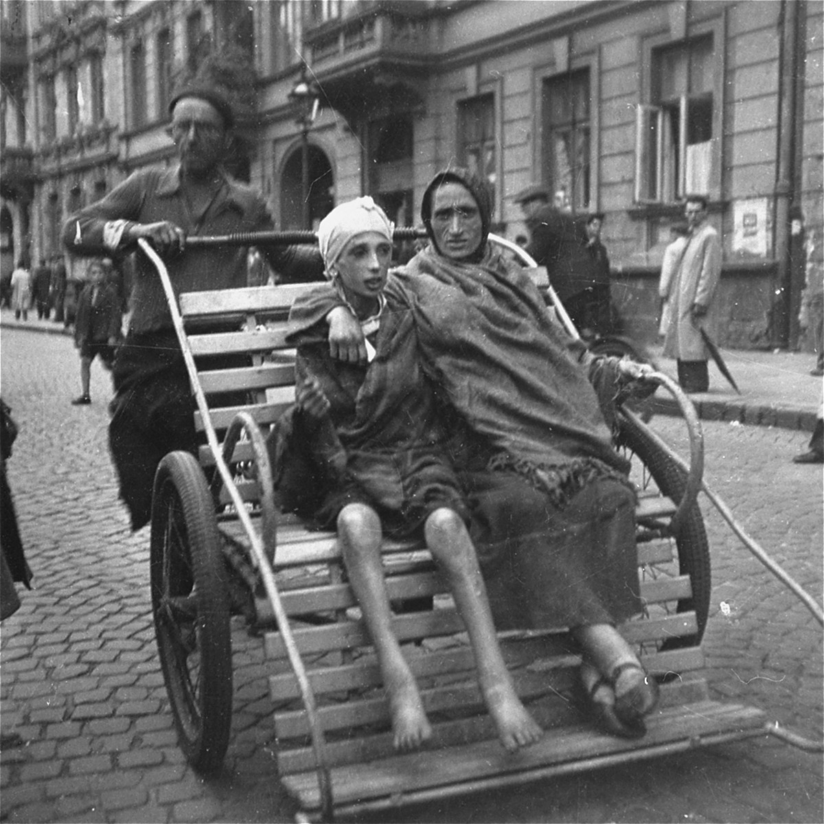 """A woman and her ill child on a rickshaw in the Warsaw ghetto.  Joest's caption reads: """"Where would this rickshaw driver take this child who was obviously sick with Typhus? Was there still a hospital for Jews?  No one among my German comrades could tell me."""""""