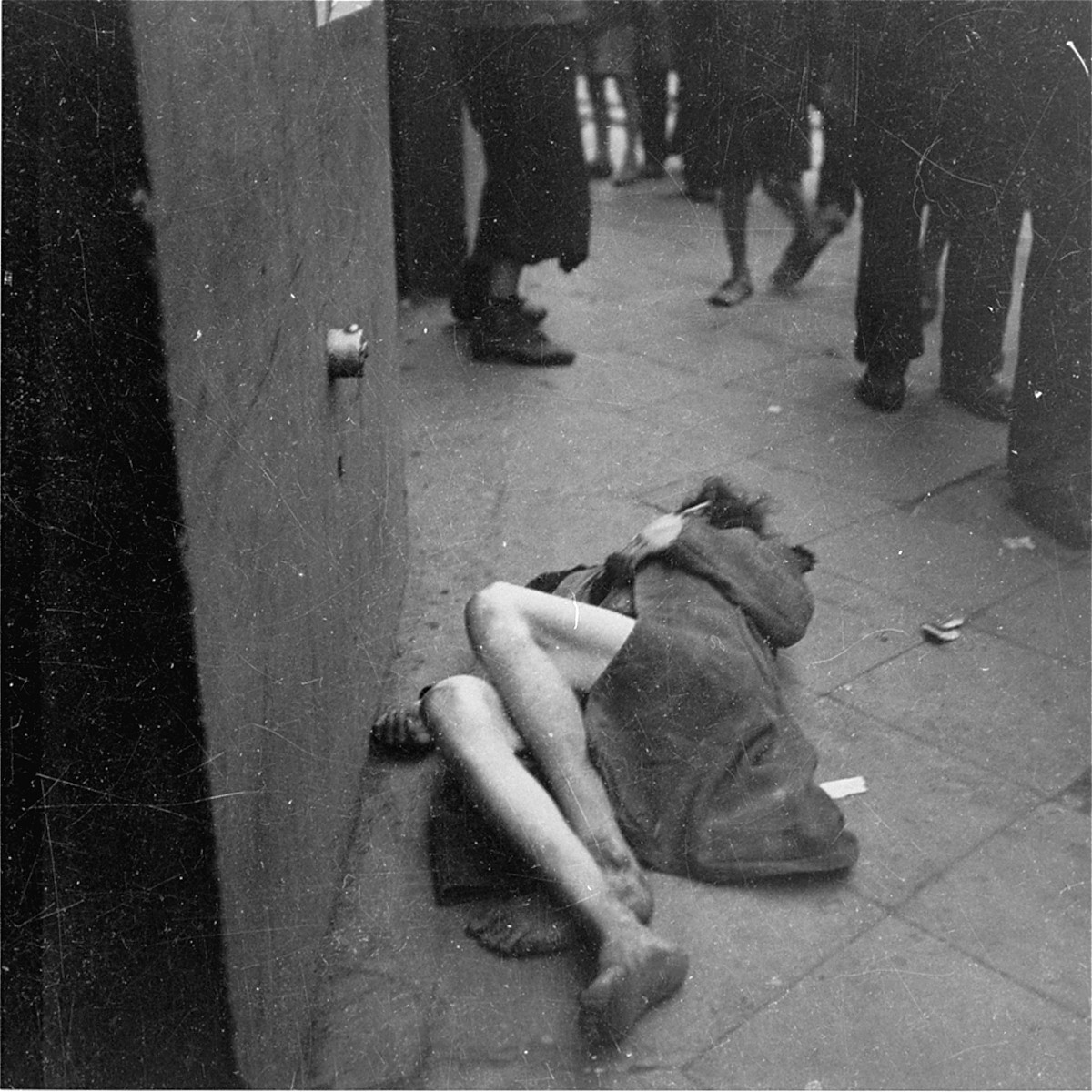 "A Jewish woman lies dead on the street in the Warsaw ghetto.    Joest's caption reads: ""This woman died before my eyes.  People stood around.  No one helped her, because no one could help."""