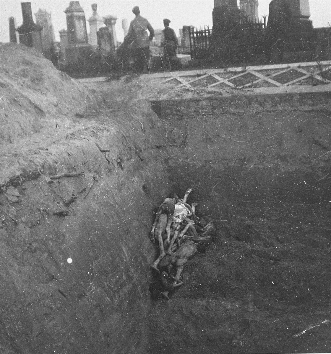 """After unloading the grim contents of their cart, gravediggers in the Warsaw ghetto cemetery leave to collect more bodies for burial in a mass grave.    Joest's caption reads: """"As soon as the body-cart was empty, it went back again for more."""""""