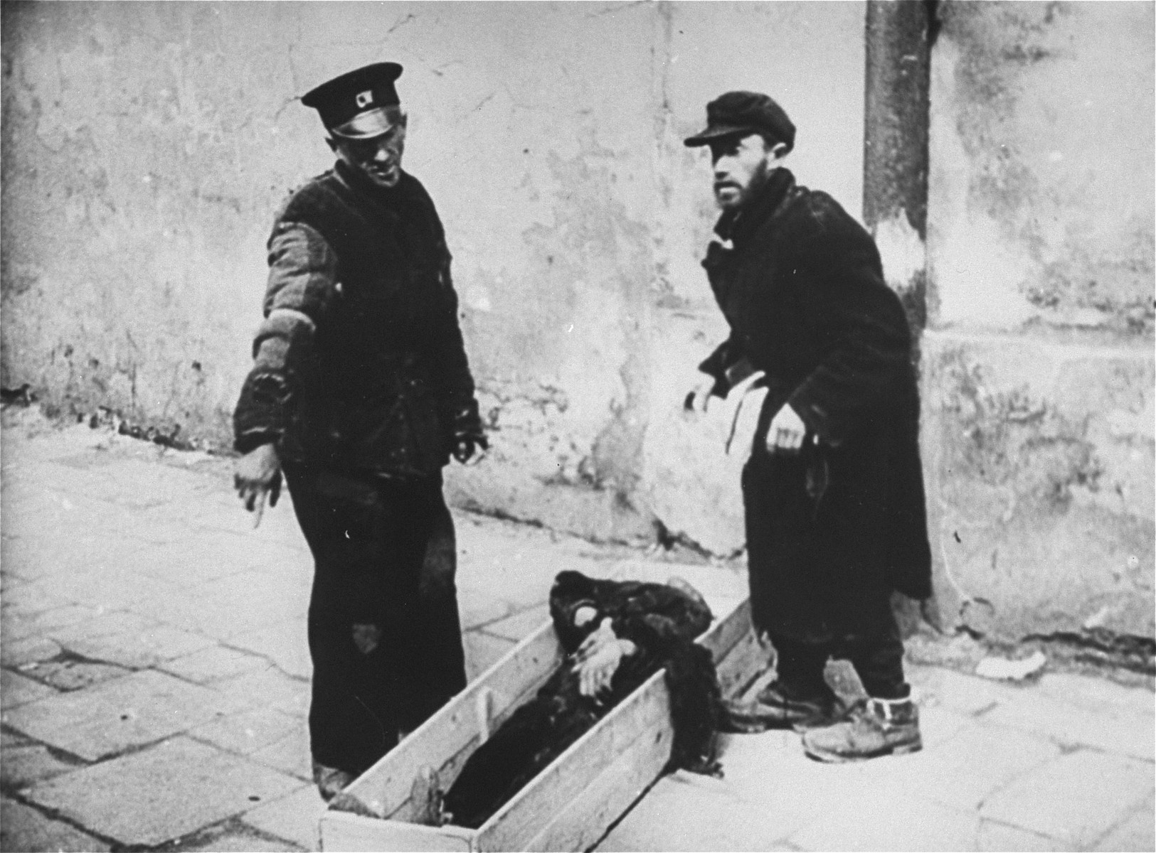 A workman from the Pinkiert funeral home has a man on the street help him pick up a body for burial in the Warsaw ghetto cemetery.