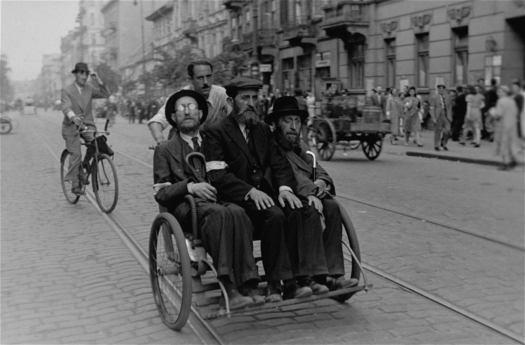 Three Jewish men ride in a rickshaw along a street in the Warsaw ghetto.