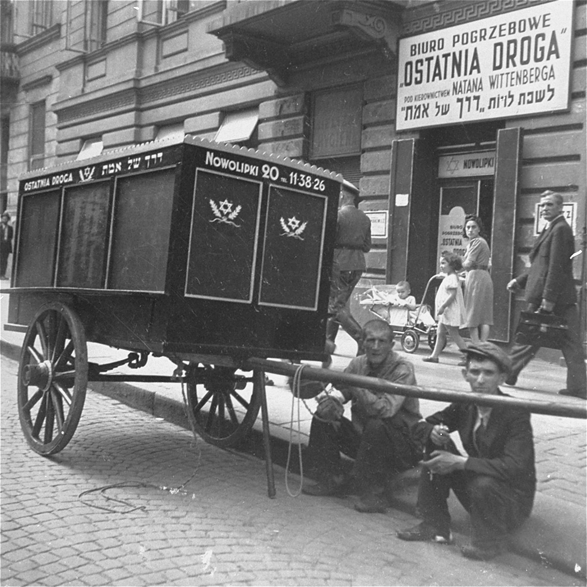 "Two workers taking a break sit next to a funeral wagon parked along Nowolipki Street in front of the offices of the Burial Society.    Joest's caption reads: ""Everywhere in the Ghetto one saw the black wagons of the undertakers.  I followed them on their way to the cemetery.  By chance I once again caught a German sergeant in the photograph."""