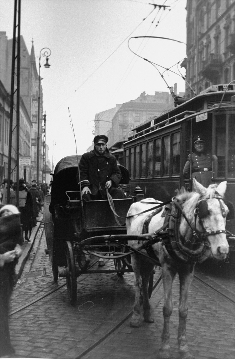 A driver leads a horse-drawn carriage along a street in the Warsaw ghetto.  Two German police officers are visible on the streetcar at right.