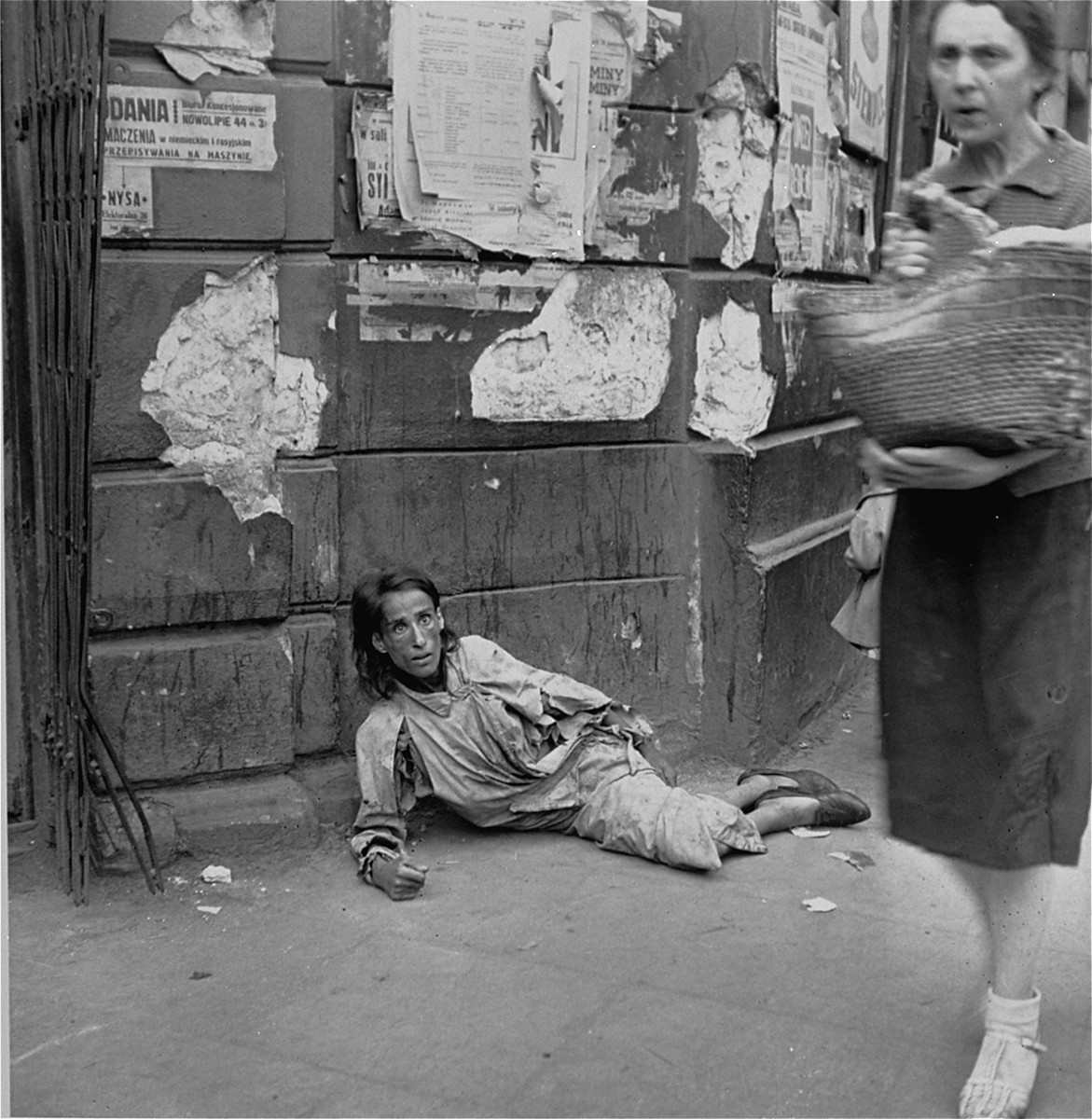 """A destitute woman lies on a sidewalk along Nowolipie Street in the Warsaw ghetto.    Joest's caption reads: """"I photographed this begging woman with fixed, staring eyes on Nowolipie Street as people went by.  [Hanging] above her was a small placard advertising an office on 44 Nowolipie Street where German and Russian could be translated."""""""
