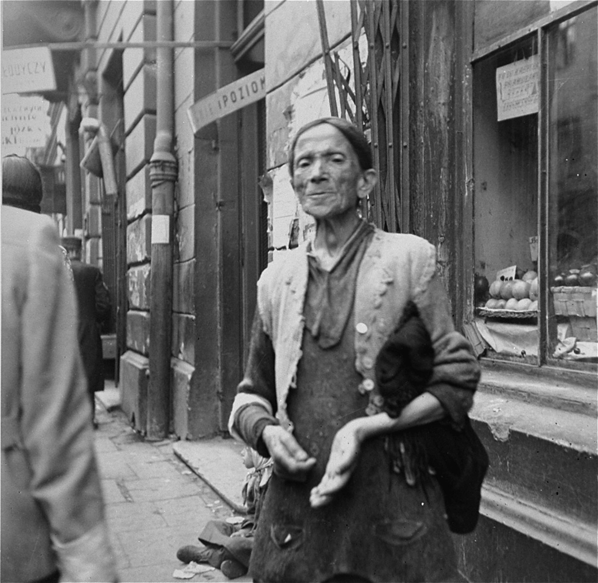 """A poor woman begs for coins or food on the street in the Warsaw ghetto.    Joest's original caption reads: """"Apples and pears in the display window behind her, this woman waited for a coin.  On the curb beside her sat her child."""""""
