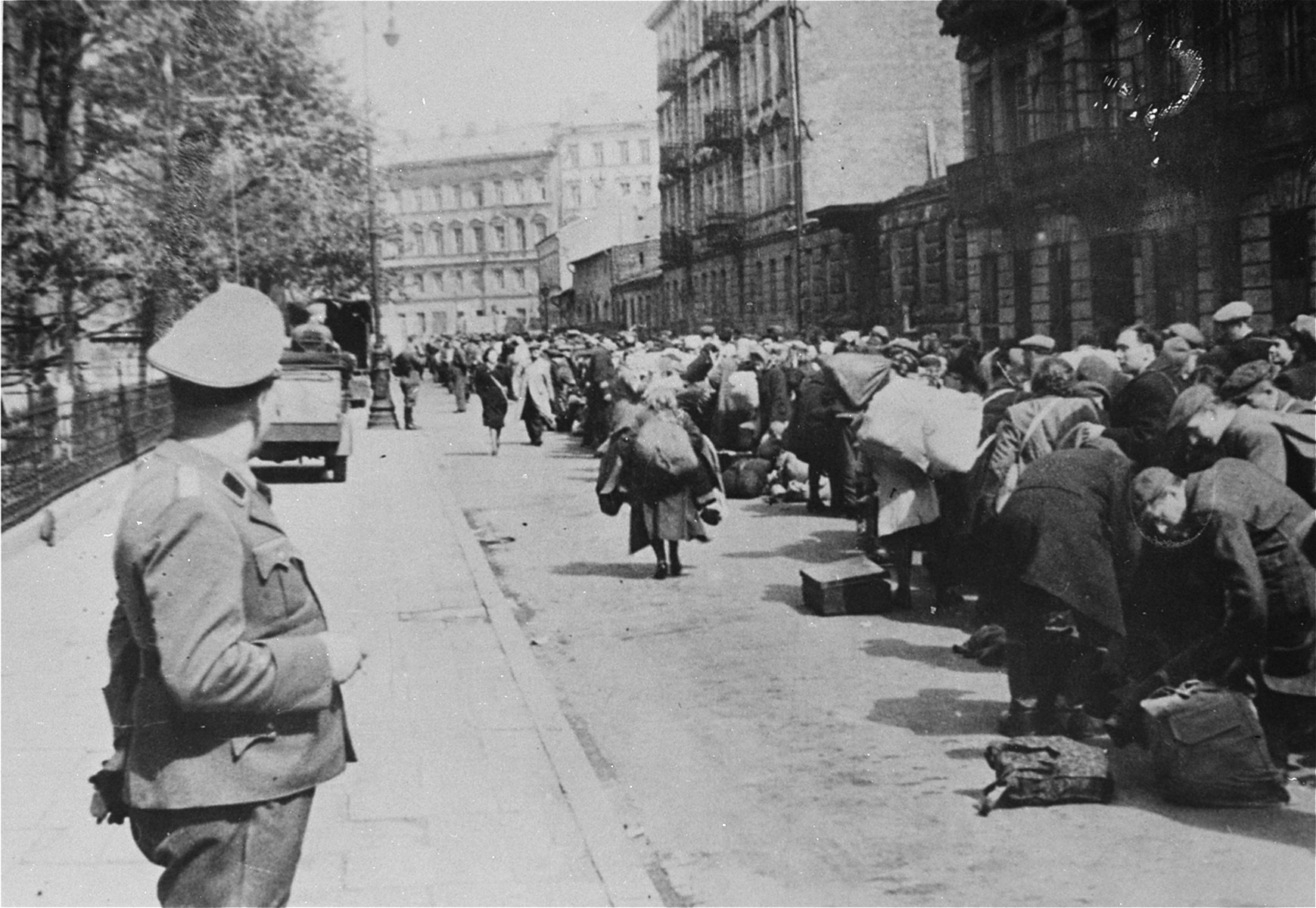 A long column of Jews who have been rounded-up for deportation walk with their luggage along a street in the Warsaw ghetto.