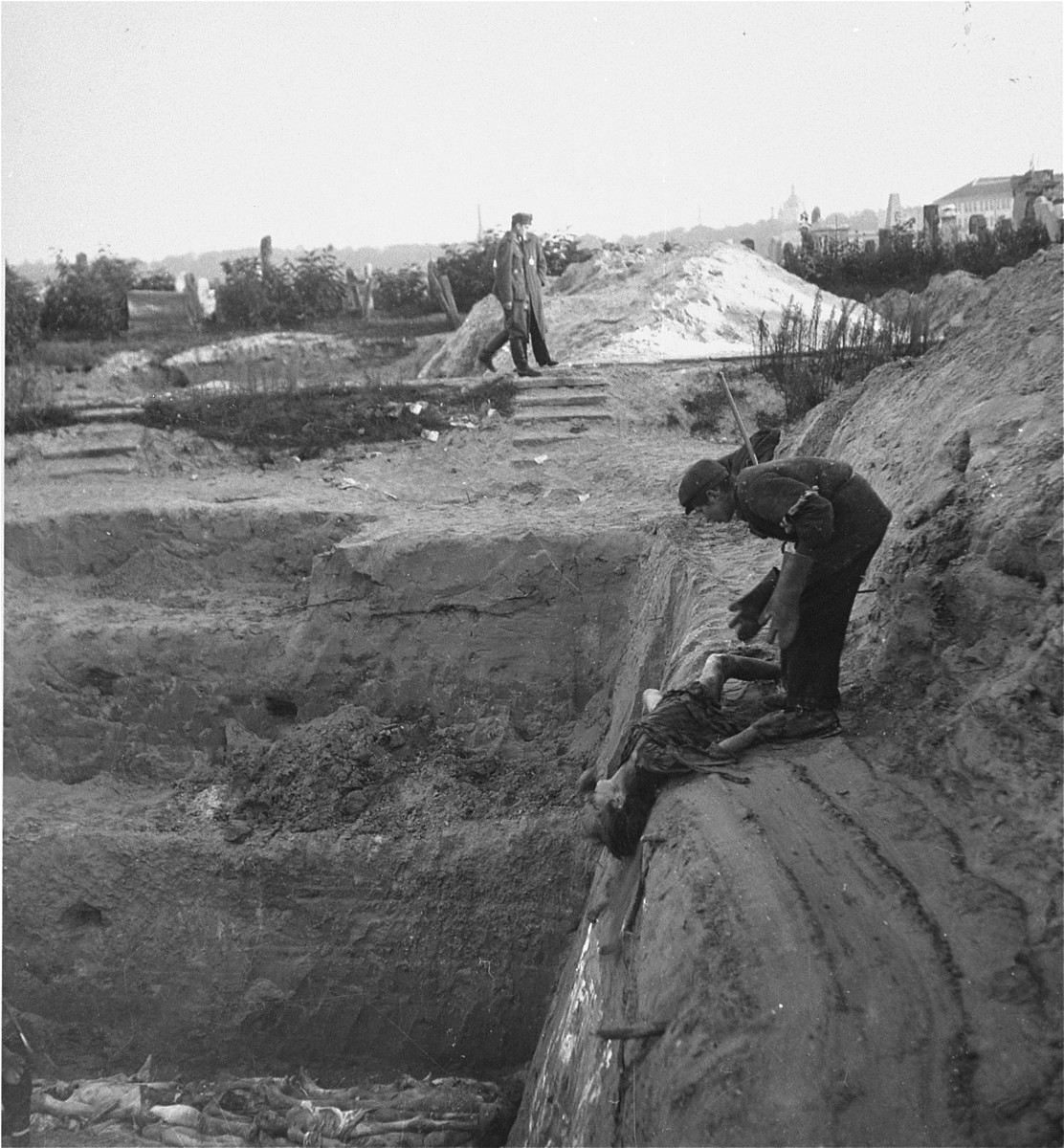 "A boy at work in the Okopowa Street cemetery in the Wasraw ghetto pushes a body into a mass grave as two officers Joest claims were from the SD (Security Service) walk by.    Joest's caption reads: ""When I was personally in the cemetery, where the bodies were being thrown into an enormous grave, I saw the SD men in the background."""
