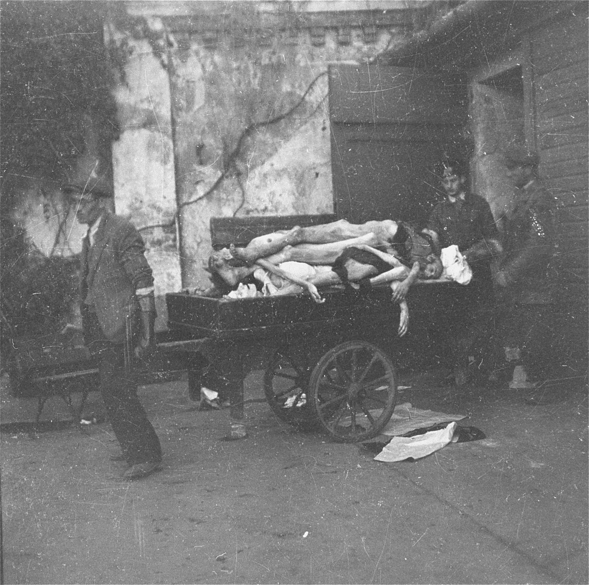 "Undertakers at work in the Jewish cemetery on Okopowa Street in the Warsaw ghetto pull a cart laden with corpses out of the morgue for burial in a mass grave.    Joest's caption reads: ""Once again a cart laden with bodies was led out, so full that the bodies hung over the side.  I thought one would surely fall off soon."""