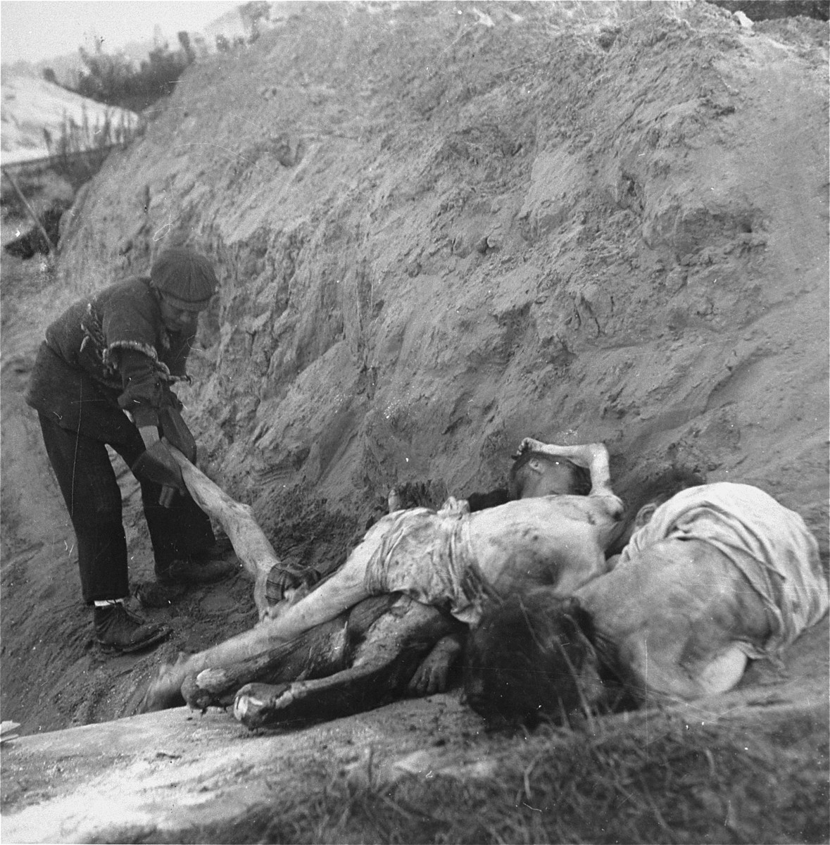 """A boy working in the Warsaw ghetto cemetery drags a corpse to the edge of the mass grave where it will be buried.    Joest's caption reads: """"It was hard work to pull the bodies to the edge of the grave.  This youth wore enormous rubber gloves."""""""