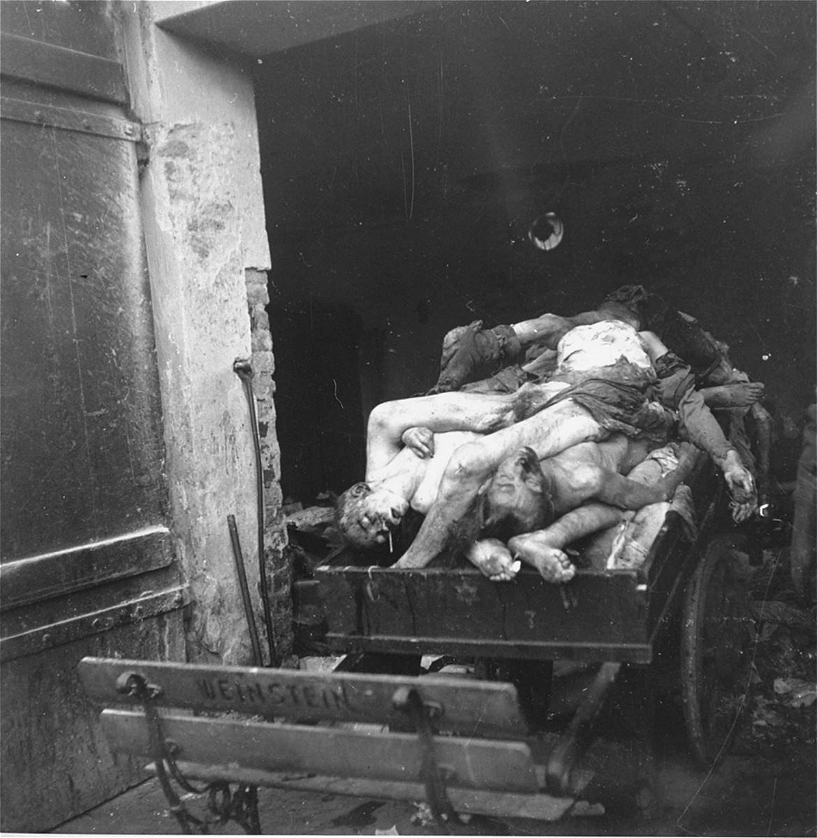 """A corpse-laden wagon stands just inside the morgue of the Jewish cemetery on Okopowa Street in the Warsaw ghetto.    Joest's caption reads: """"One of the corpse-bearers opened the door of the shed so I could take photos.  It was an unsettling picture."""""""