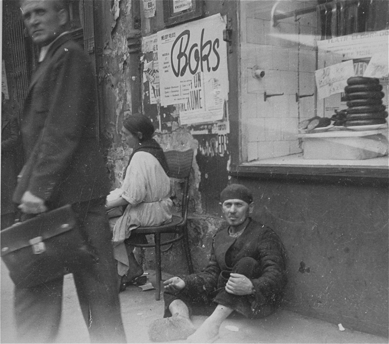"""A man begs for change or food while sitting in front of a butcher shop on Nowolipie Street in the Warsaw ghetto.  Joest's caption reads: """"It was incomprehensible, sausages were stacked in the display window of the butcher shop on Nowolipie Street , and in front of them sat a hungry beggar."""""""