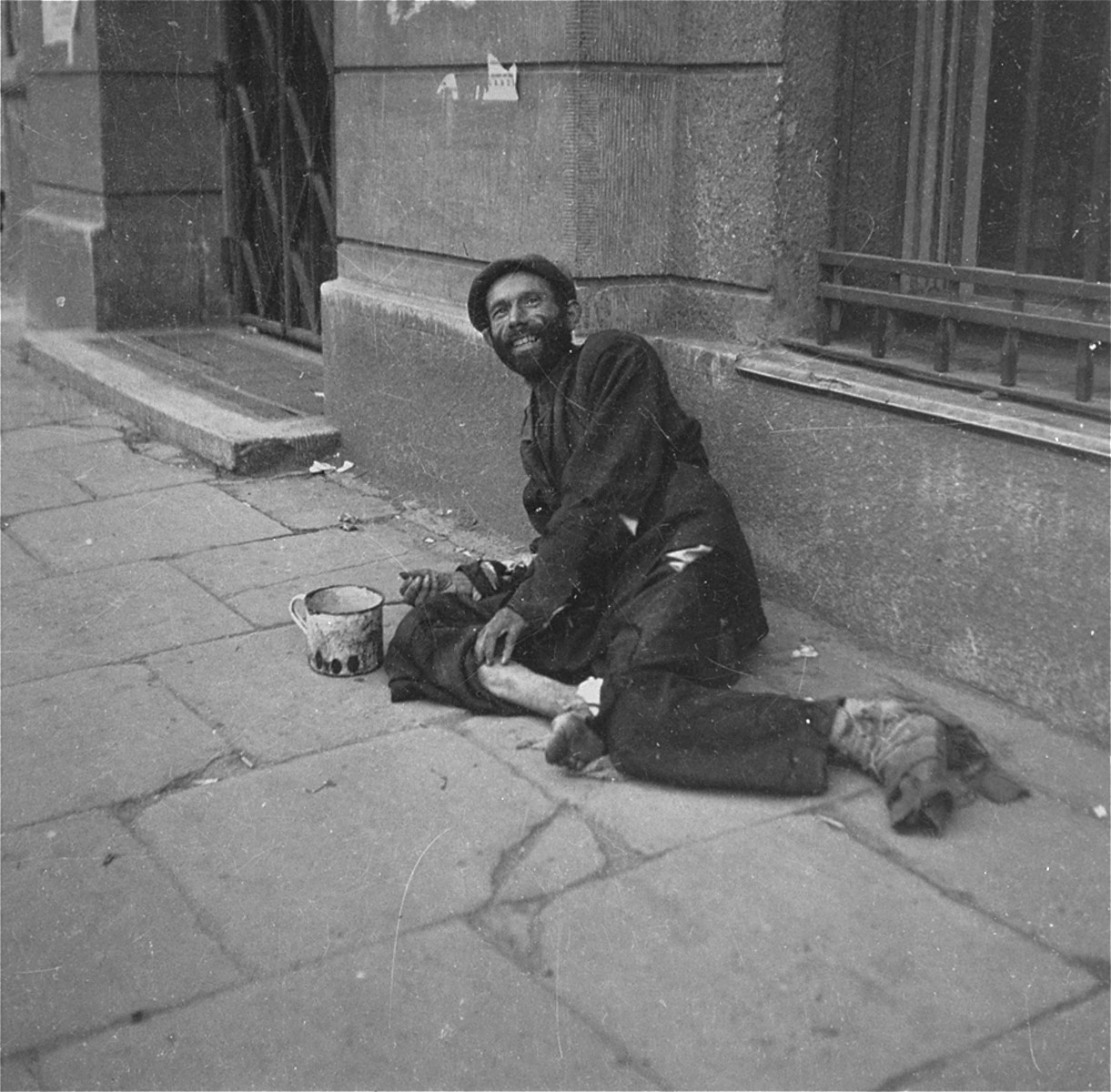 "A destitute beggar on the street in the Warsaw ghetto.    Joest's caption reads: ""I do not know if this man was truly laughing, or if he only grinned at me out of fear.  He stank dreadfully of rotting flesh."""
