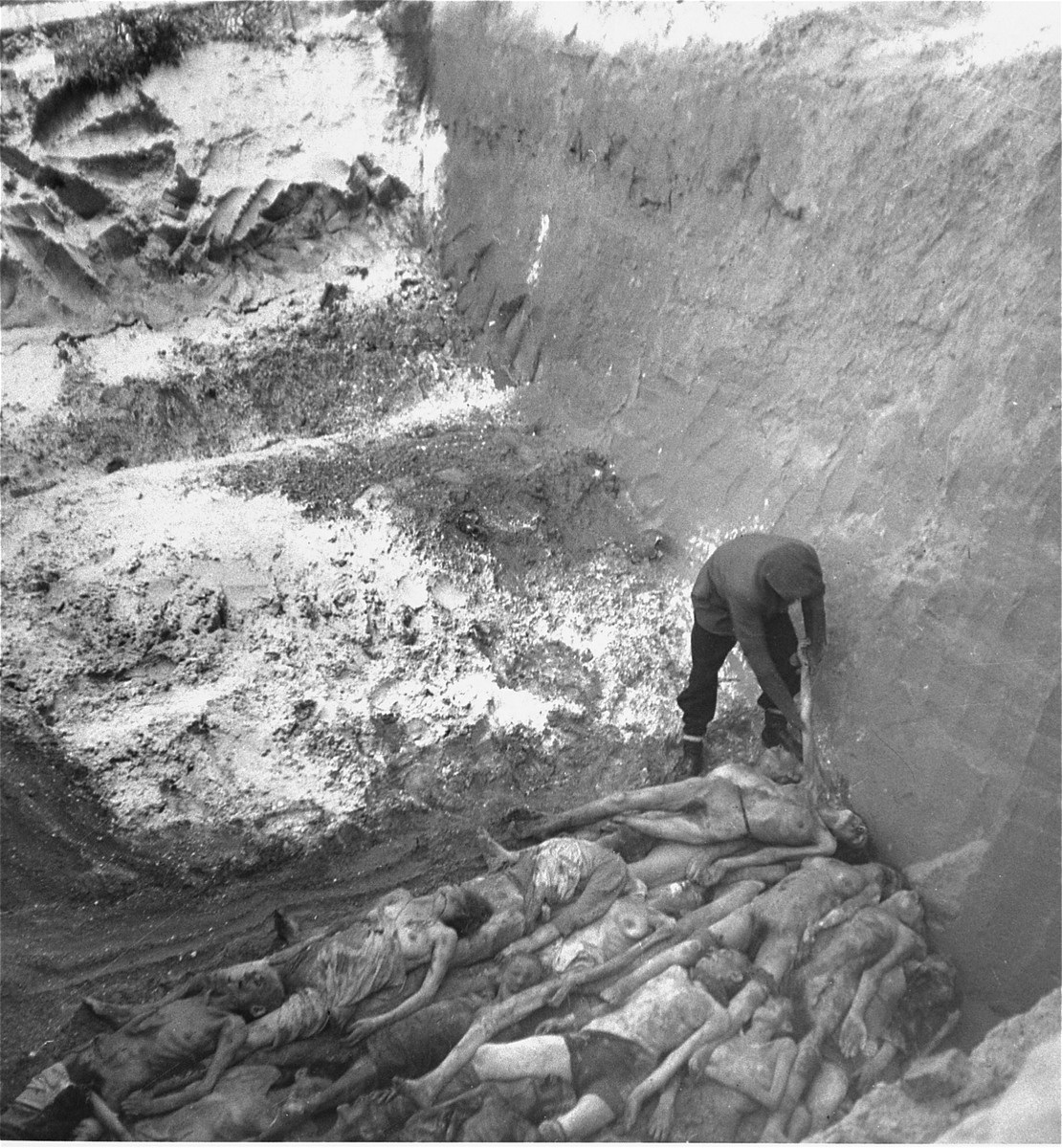 "A gravedigger arranges bodies at the bottom of a large mass grave in the Okopowa Street cemetery in the Warsaw ghetto.    Joest's caption reads: ""Many of the dead still had on little pieces of clothing, shirts and underwear."""