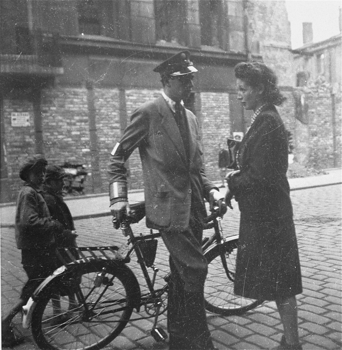 """A Jewish policeman speaks with a woman on the street in the Warsaw ghetto.    Joest's captions reads: """"It looked like a flirtation, this brief encounter between a young woman and the handsome policeman, but the begging children in the background provided a contrast."""""""