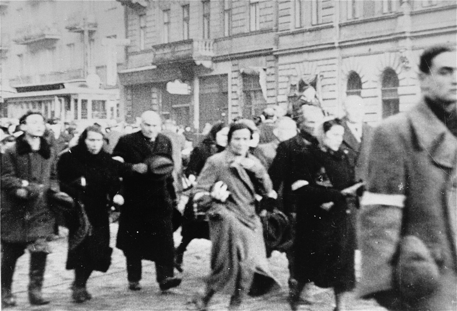 Jews who have been rounded-up for deportation in the Warsaw ghetto walk along a street to the assembly area.
